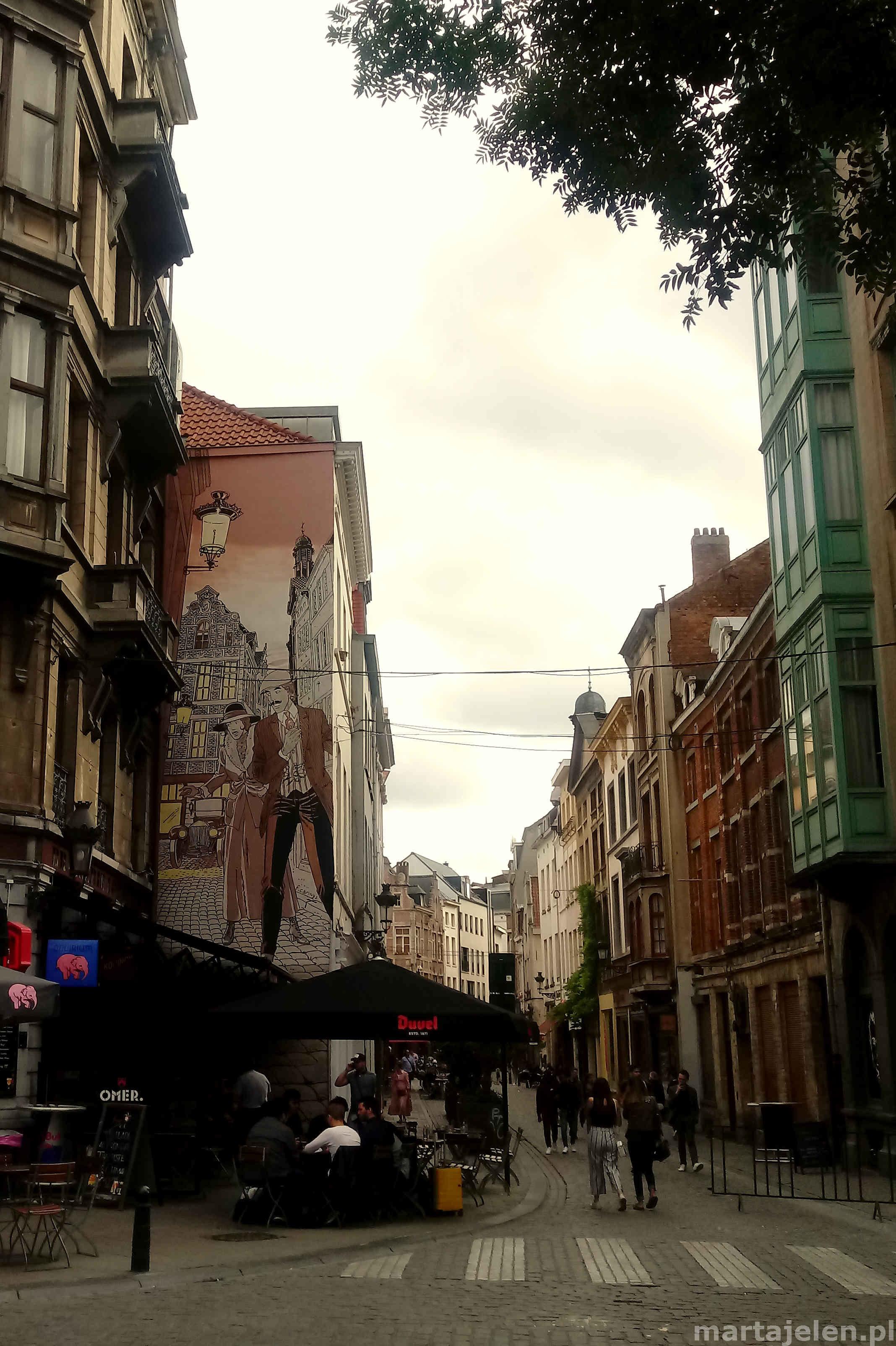 Widok na ulicę Brukseli z kamienicą, na której widnieje komiksowy mural