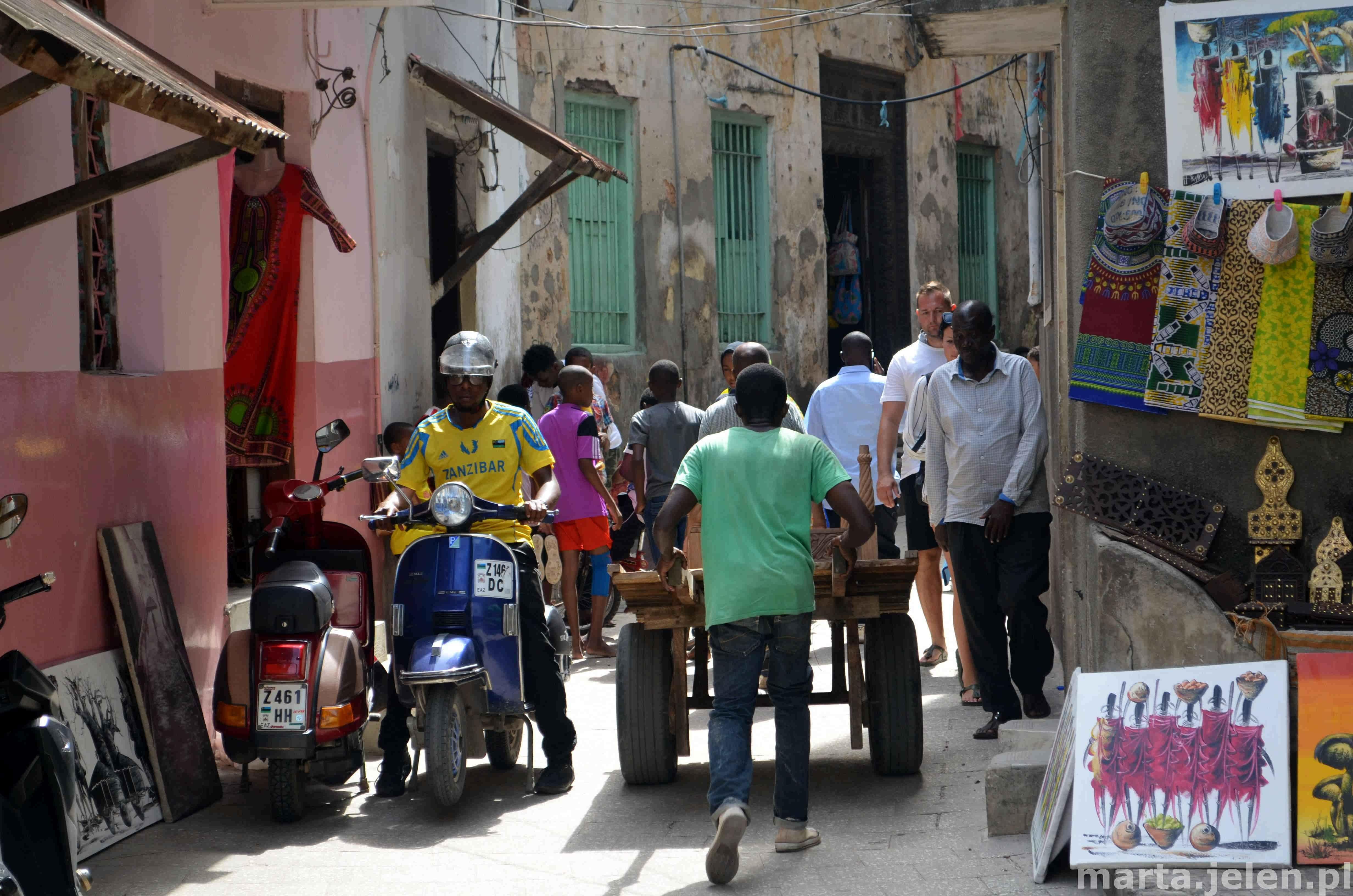 Zatłoczona uliczka w centrum starego miasta stolicy Zanzibaru ze sklepikami
