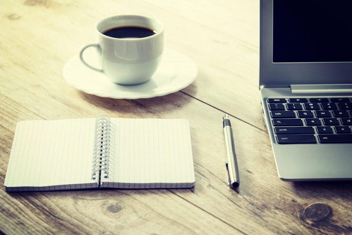 Kawa notatnik i laptop na biurku